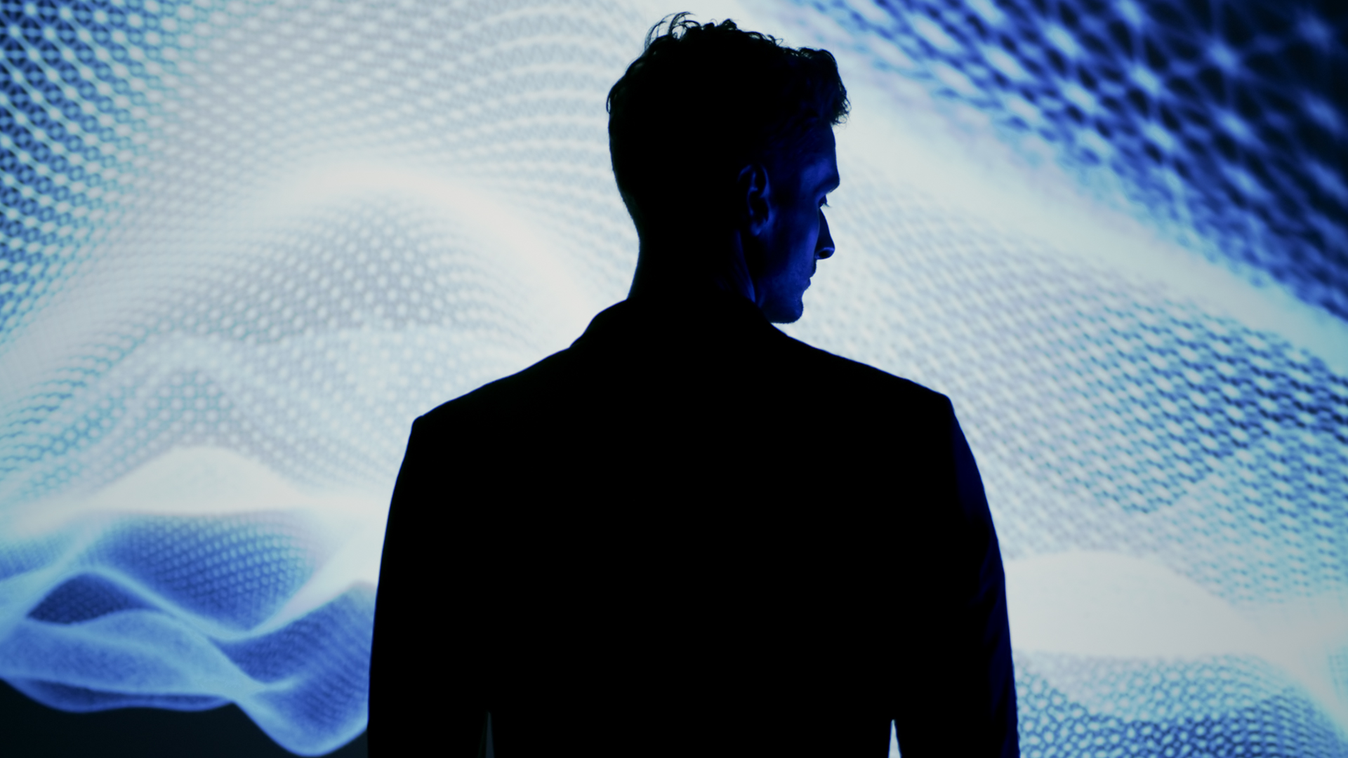 Screenshot of man in front of projection from 'Vinfast - Between Worlds' TV commercial